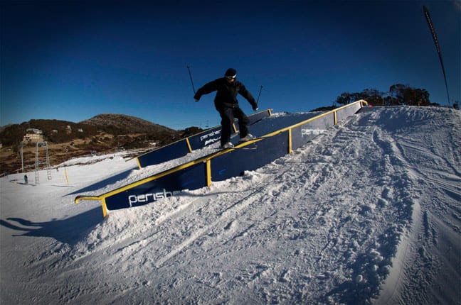 Boen Ferguson enjoying the PlayStation terrain park at Perisher - beyond the snowmaking areas the hills are very green. Image: Ben Hansen