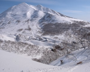 "Justin ""Grover"" Graves followed by his loyal dog, Mr. Winston. This area of the Niseko backcountry is just a short drive from the resort and offers views of the backside of Mt. Niseko-Annupuri and a plethora of peaks to hike and ride."
